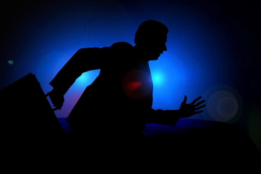 silueta de un hombre corriendo con un maletín en la noche